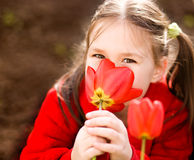 Little girl smelling flowers outdoors Royalty Free Stock Images