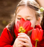 Little girl smelling flowers outdoors Stock Photos