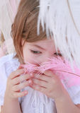 Little girl smelling a pink feather Stock Photo