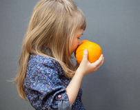 Little girl smelling a ripe oranges Stock Images
