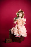 Little girl smelling rose flower. Portrait of little girl smelling rose flower sitting on wooden trunk against red background Royalty Free Stock Photos