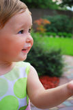 Little girl smile. Little girl play on the yard. She look ahead and smile. Her hand direct to her view. Maybe she give some somebody stock photo