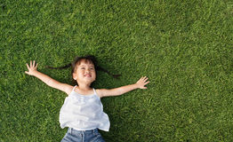 Little girl smile. Asian little girl smile and lay on grass Royalty Free Stock Images