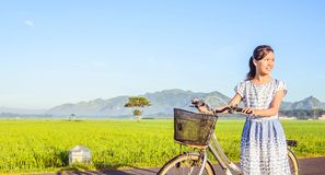 A little girl smile with a bicycle in the field royalty free stock photography