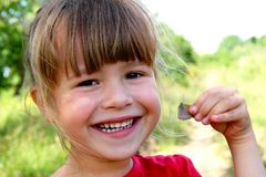 Little girl smile at the camera. Portrait of happy, positive, sm. Iling, playful caucasian girl with butterfly in her hand Stock Photo