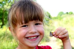 Little girl smile at the camera. Portrait of happy, positive, sm. Iling, playful caucasian girl with butterfly in her hand Royalty Free Stock Photo