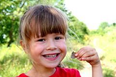 Little girl smile at the camera. Portrait of happy, positive, sm. Iling, playful caucasian girl with butterfly in her hand Royalty Free Stock Image