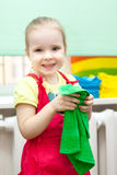 Little girl with smile on face in sundress with green towel in hands Royalty Free Stock Image