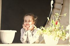 Little girl smile with flowers on sunny day. Happy child and childhood. Beauty kid with plant pots in summer or spring stock photography