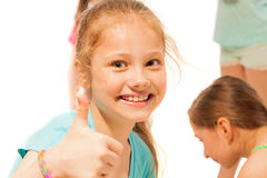 Little girl smile and thumb up  with friends. Nice smiling beautiful portrait of school age girl isolated on white with thumb up gesture Royalty Free Stock Photo