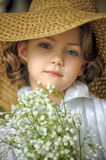 Little girl with a smile in a wide-brimmed straw hat in a bouquet of white lilies of the valley in the hands Stock Images