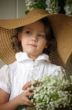 little girl with a smile in a wide-brimmed straw hat in a bouquet of white lilies of the valley in the hands Royalty Free Stock Photography