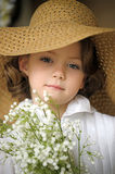 Little girl with a smile in a wide-brimmed straw hat in a bouquet of white lilies of the valley in the hands. Art studio portrait of little pretty girl Stock Photography