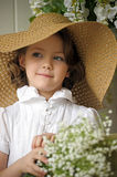Little girl with a smile in a wide-brimmed straw hat in a bouquet of white lilies of the valley in the hands. Art studio portrait of little pretty girl Royalty Free Stock Photo