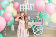 Little girl smiles and closes his eyes in a studio. A portrait of a beautiful little girl smiles and closes his eyes in a studio decorated many color balloons Stock Photos