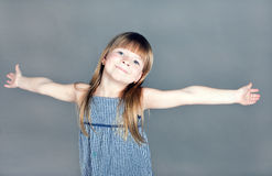 The little girl smiles happily spreading his hands Royalty Free Stock Photo