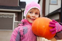 Little girl smiles and holds pumpkin Stock Photo