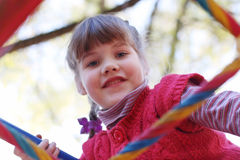 Little girl smiles on ladder of playground Stock Photo