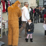 Little girl smiles at a man dressed in a yeti costume Royalty Free Stock Photos