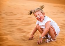 Little girl smiles and plays sand stock images