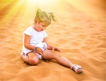 Little girl smiles and plays sand royalty free stock photography