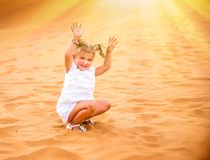 Little girl smiles and plays sand royalty free stock photo
