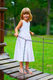 Little girl smiles while standing on the bridge Stock Image