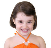 Little girl smiling. Girl dressed in orange Stock Photo