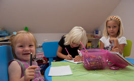 Little girl smiling. While her sisters draw Stock Photos