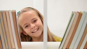 Little girl smiling through a bookshelf stock footage
