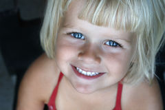 Little girl smiling at camera. A four year old girl smiling up towards the camera. Horizontal soft image with blurred background Stock Photos