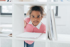 Little girl smiling at camera through bookshelves in office Royalty Free Stock Photos