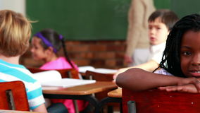 Little girl smiling at the camera during class. In elementary school stock video footage
