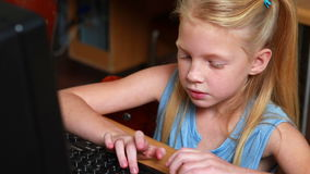 Little girl smiling at camera during computer class. In elementary school stock video