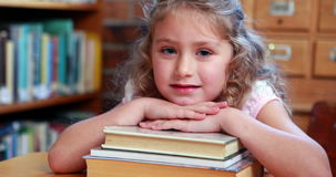 Little girl smiling at camera in the library. In elementary school stock video footage
