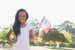 Little girl smiling at camera waving american flag Royalty Free Stock Photo