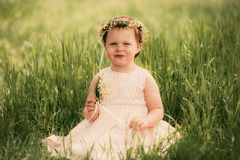 Little girl smiling, child sitting on the grass Royalty Free Stock Photography