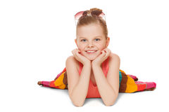 Little girl smiling in colorful skirt is lying. Happy child with hands near face, isolated on white background Stock Photo