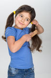 Little girl smiling and combing hair. Royalty Free Stock Image