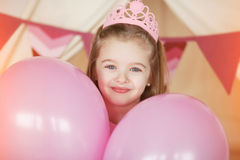 Little girl smiling between decorated pink colorful balloons Royalty Free Stock Image