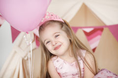 Little girl smiling between decorated pink colorful balloons. A portrait of a beautiful little girl smiling between decorated pink colorful balloons. Cute kid Royalty Free Stock Images