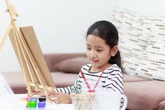 The little girl smiling and draws a picture at home stock image