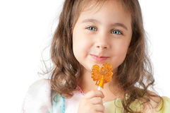 Little girl smiling and eating candy Stock Photos