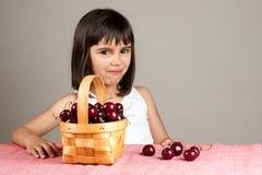 Little girl smiling while eating cherries Stock Image