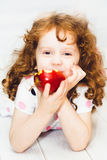 Little girl smiling and eating a red apple Stock Photos