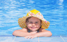 Little girl smiling on the edge of the swimming pool Royalty Free Stock Photos