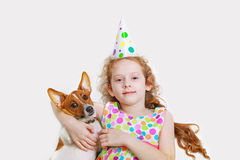 Little girl is smiling and embracing her friend pet, lying on li. Ght background. Happy holiday and childhood concept Royalty Free Stock Photos
