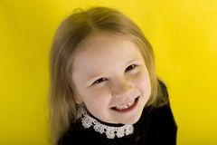 Little girl is smiling. emotions. on yellow background. top view. Little girl blonde in black dress smiling. emotions. on yellow background. top view royalty free stock image