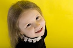Little girl is smiling. emotions. on yellow background. top view stock image