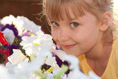 Little girl smiling  and the flowers Royalty Free Stock Photo